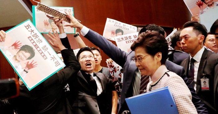 """Các nghị viên đối lập ở Hồng Kông đưa hình Trưởng Đặc Khu Carrie Lam với đôi tay """"vấy máu"""" trong nghị trường."""