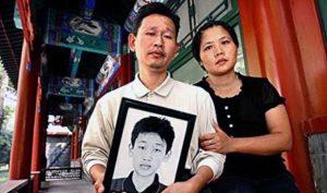 Liêu Tổ Sanh ôm di ảnh của người con Liêu Mộng Quân bị chính quyền bức hại.