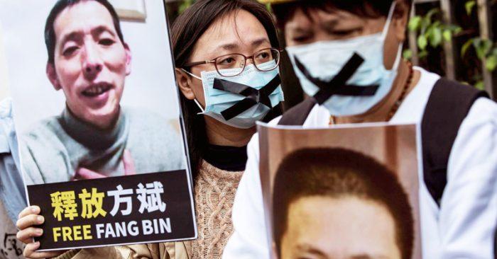 Một nhà hoạt động dân chủ (giữa) từ Liên minh HK giữ một tấm bảng của nhà báo công dân mất tích Phương Bân (Fang Bin), khi cô biểu tình bên ngoài văn phòng liên lạc Trung Quốc tại Hồng Kông vào ngày 19 tháng 2 năm 2020.
